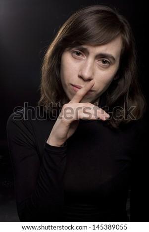 sad woman on black background - stock photo