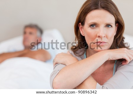 Sad woman on the bed with her husband in the background