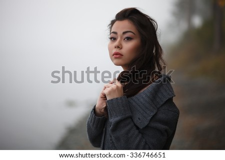 Sad woman outdoors movie-styled. Thoughtful young woman wearing muffler at lakeside in park - stock photo