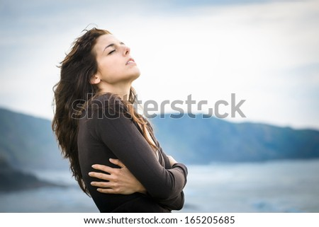 Sad woman shivering and feeling the sea breeze. Nostalgic and emotional female hugging herself and feeling low on cold late summer or autumn day. Beautiful curly hair caucasian model. - stock photo