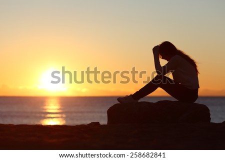 Sad woman silhouette worried on the beach at sunset with the sun in the background - stock photo