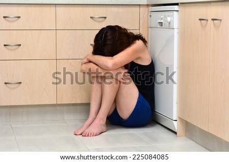 Sad woman sit in her kitchen and covering her face after domestic violence - stock photo