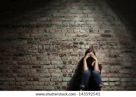 Sad woman sitting alone against brick wall. - stock photo