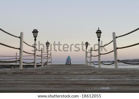 Sad woman sitting alone on a jetty - stock photo
