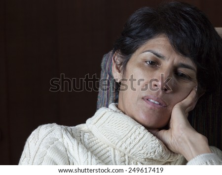 Sad woman sitting in chair with copy space - stock photo