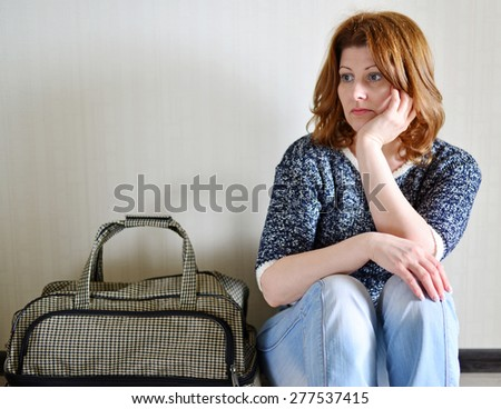 Sad woman sitting near the wall with a suitcase because divorce - stock photo