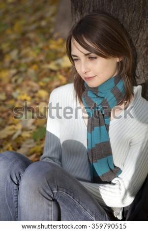 sad woman sitting nearby tree in autumn park - stock photo