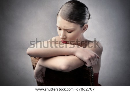 Sad woman sitting on a chair - stock photo