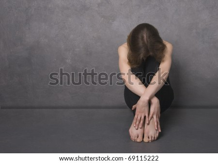 Sad woman sitting on a floor near concrete wall, studio shot - stock photo