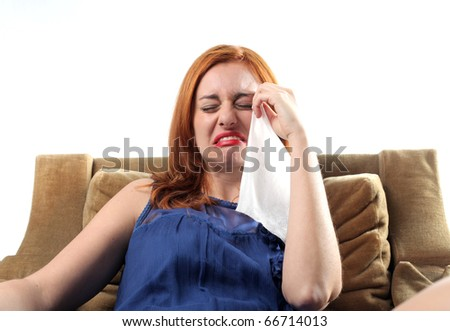 Sad woman sitting on an armchair and crying - stock photo