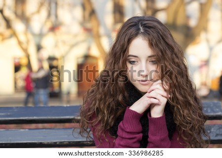 sad woman sitting on bench in a park
