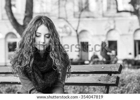 sad woman sitting on bench in a park - stock photo