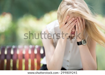 Sad woman sitting on bench outdoors - stock photo