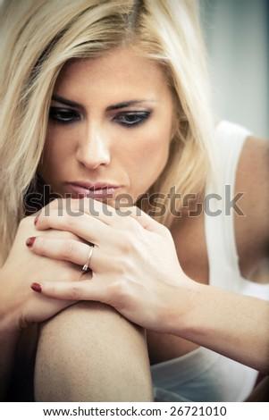 sad woman sitting on sofa with knees bent - stock photo