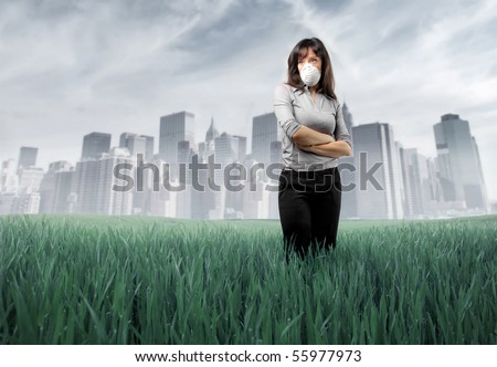 Sad woman wearing a surgical mask with polluted green meadow and city on the background - stock photo