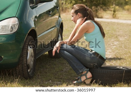 sad woman with a broken car sitting on tire