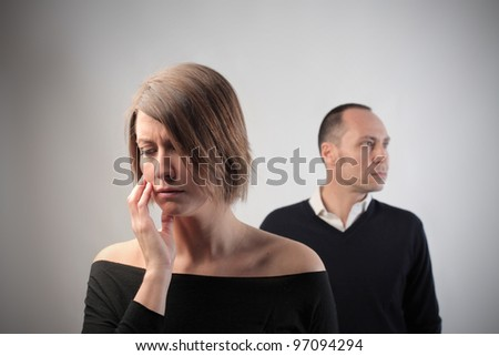 Sad woman with angry husband in the background