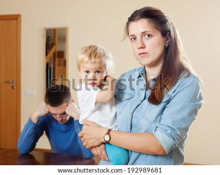 Sad woman with baby against husband after quarrel at home - stock photo