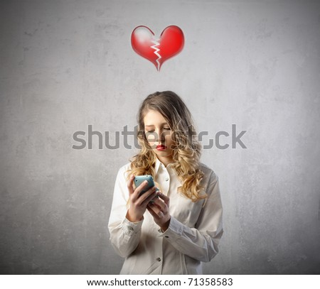 Sad woman with broken heart looking at her mobile phone