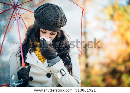 Sad woman with cold or flu blowing her nose with a tissue under autumn rain. Brunette female sneezing and wearing warm clothes against cold weather. Illness, depression and allergy concept. - stock photo