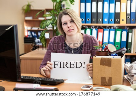 """Sad woman with collected things and sheet of paper with word """"Fired"""" - stock photo"""