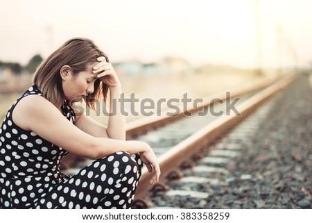 Sad woman with depression sitting on railway track - stock photo