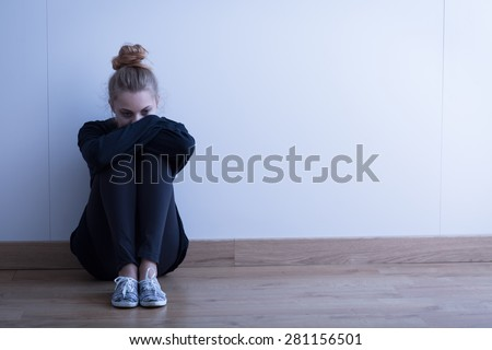 Sad woman with depression sitting on the floor - stock photo