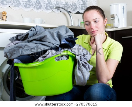 Sad woman with dirty clothes near washing machine - stock photo