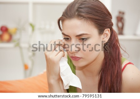 sad woman with handkerchief crying on sofa