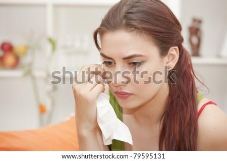 sad woman with handkerchief crying on sofa - stock photo