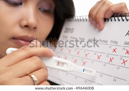Sad woman with negative pregnancy test and calendar. A concept being failed to get pregnant - stock photo