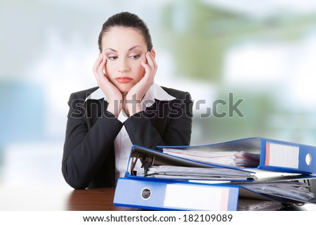 Sad woman with ring binders sitting at the desk. Tired and exhousted business woman.  - stock photo