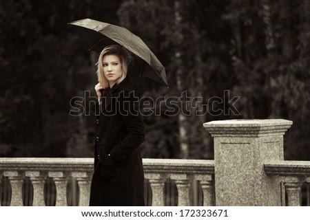 Sad woman with umbrella in the rain - stock photo