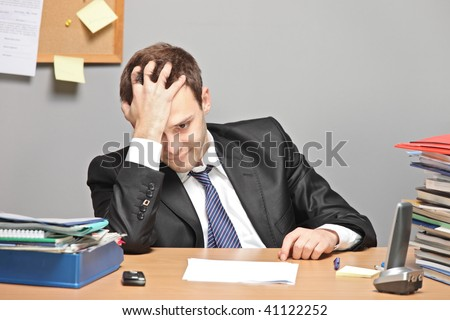 Sad worker in an office - stock photo