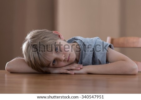 Sad worried boy lying on the table - stock photo