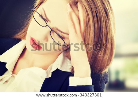 Sad, worried caucasian business woman sitting - stock photo