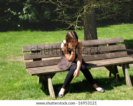 Sad/worried girl sitting on a wooden bench in a park all alone.