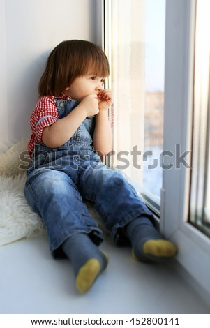 Sad 2 years boy sits on sill and looks out of window in wintertime - stock photo