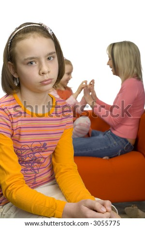 Sad 10-12yo girl. Focus on her face. There are her mother and younger sister behind her. Girl's feeling rejected and alone. - stock photo