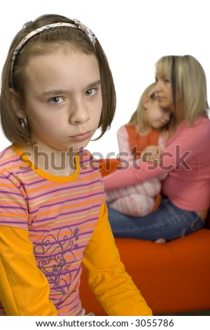 Sad 10-12yo girl. Focus on her face. There are her mother and younger sister behind her. Girl's feeling rejected and alone.