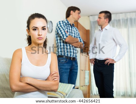 Sad young american girl having argue with her friends at home. focus on girl - stock photo