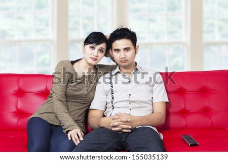 Sad young asian couple watching television at home - stock photo