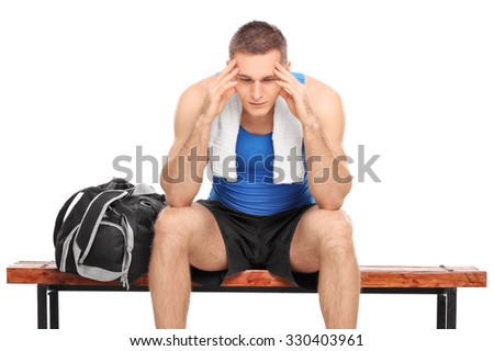 Sad young athlete sitting on a wooden bench and looking down isolated on white background - stock photo