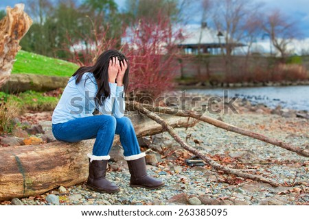 Sad young biracial teen girl in blue shirt and jeans sitting on log along rocky beach by lake - stock photo
