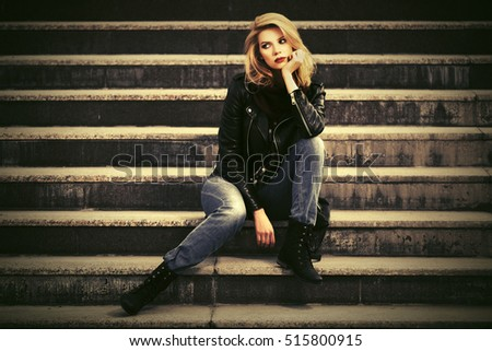 Sad young blond woman in leather jacket sitting on the steps. Stylish fashion model outdoor