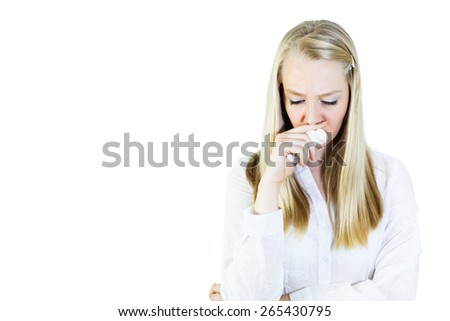 Sad,  young, blonde woman holding tissue on a nose, looking down.Isolated on white, copy space - stock photo