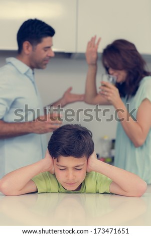 Sad young boy covering ears while parents quarreling in the kitchen at home