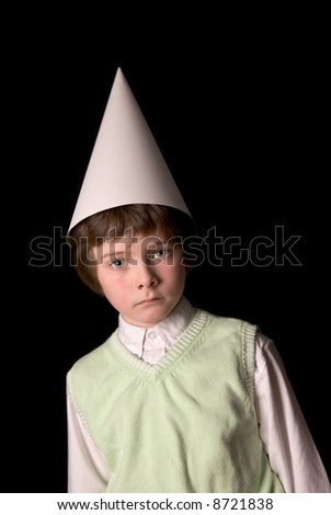 Sad young boy in a dunce cap over a black background - stock photo