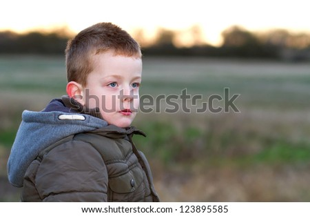 sad young boy in a field - stock photo