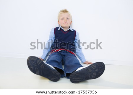 Sad young boy sitting on the floor. He's looking at camera. front view.